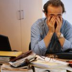 Man covering his face in office